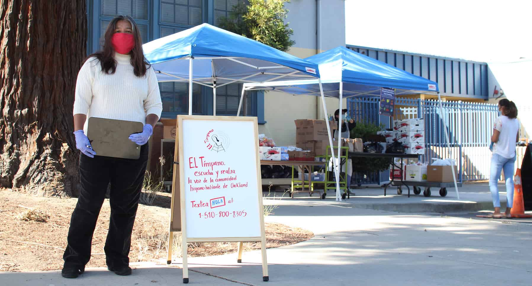 A woman stands outside a tent next to a white board advertising El Timpano