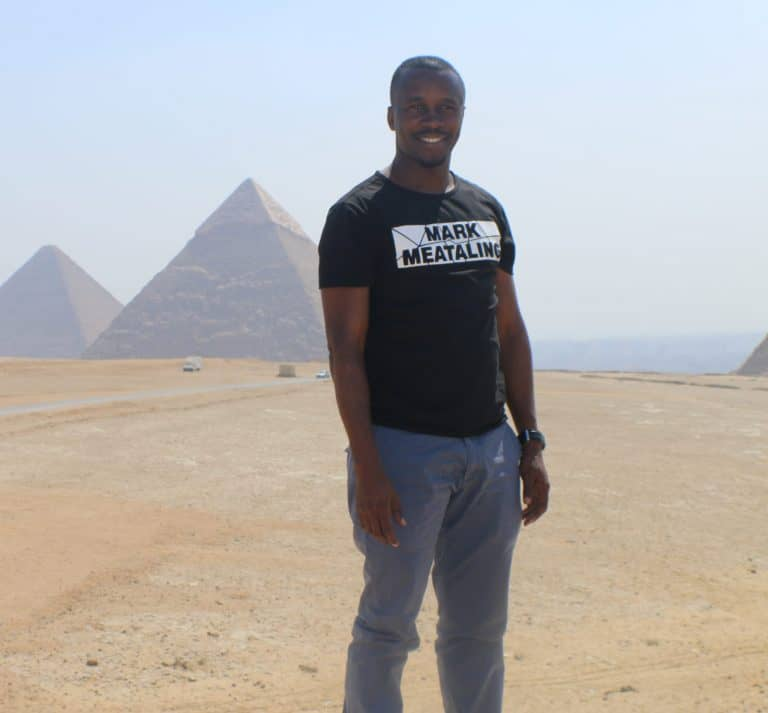 A man stands in the desert with pyramids in the background
