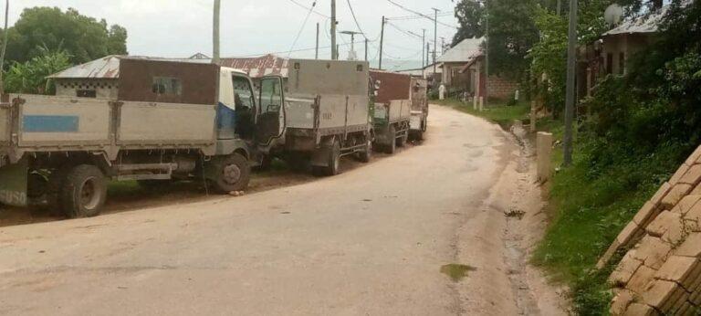 Trucks line up alongside a dirt road