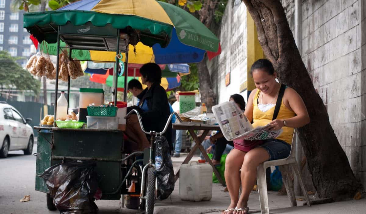A woman sits on a chair on the street reading a newspaper; she's next to a food cart.