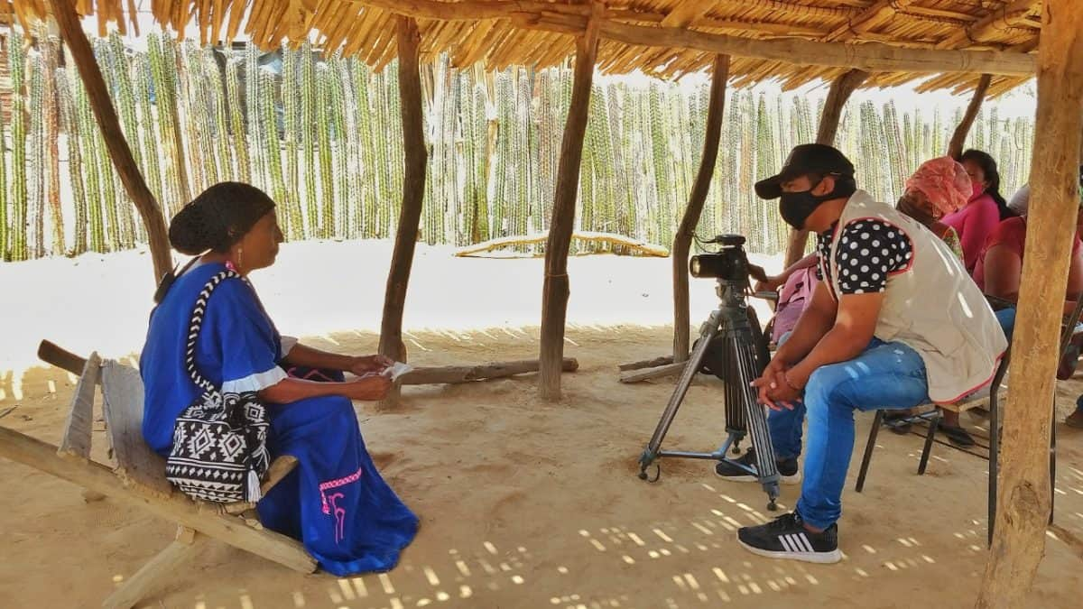 A man wearing a face mask and using a video camera sits under a tent interviewing a woman seated at a distance
