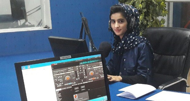 A woman sits in a radio studio
