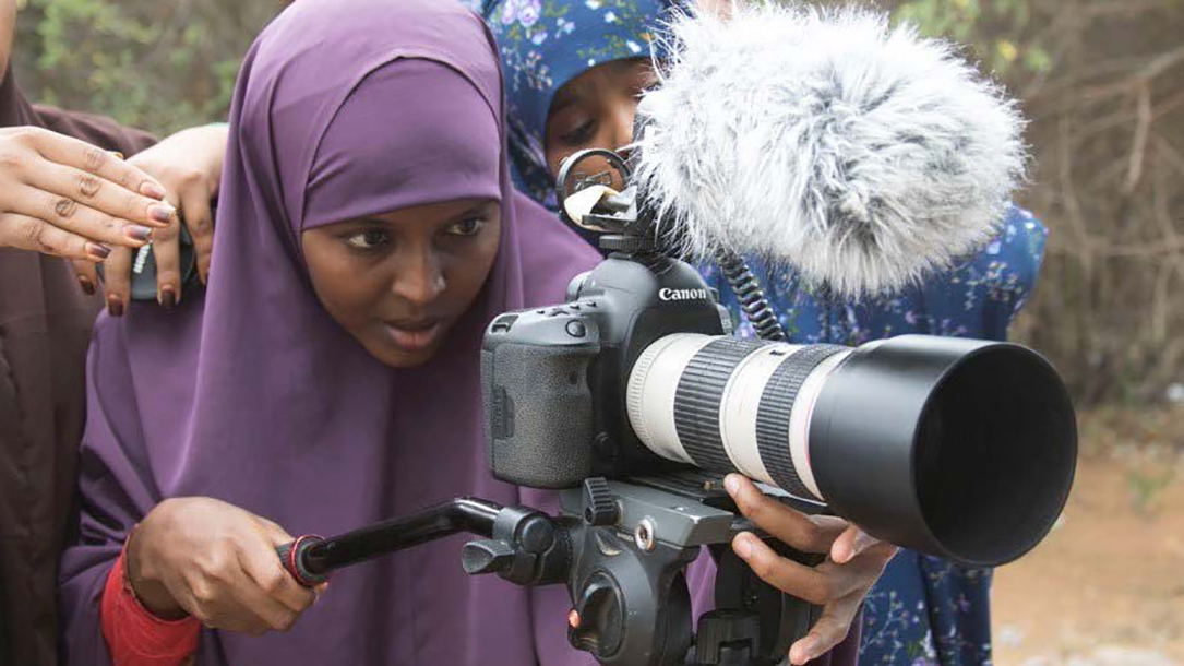 Two women look through a video camera