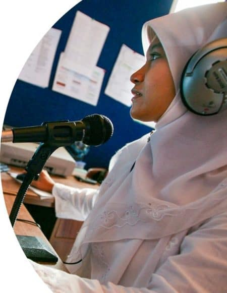 A woman wearing a head scarf and headphones sits in front of a mic