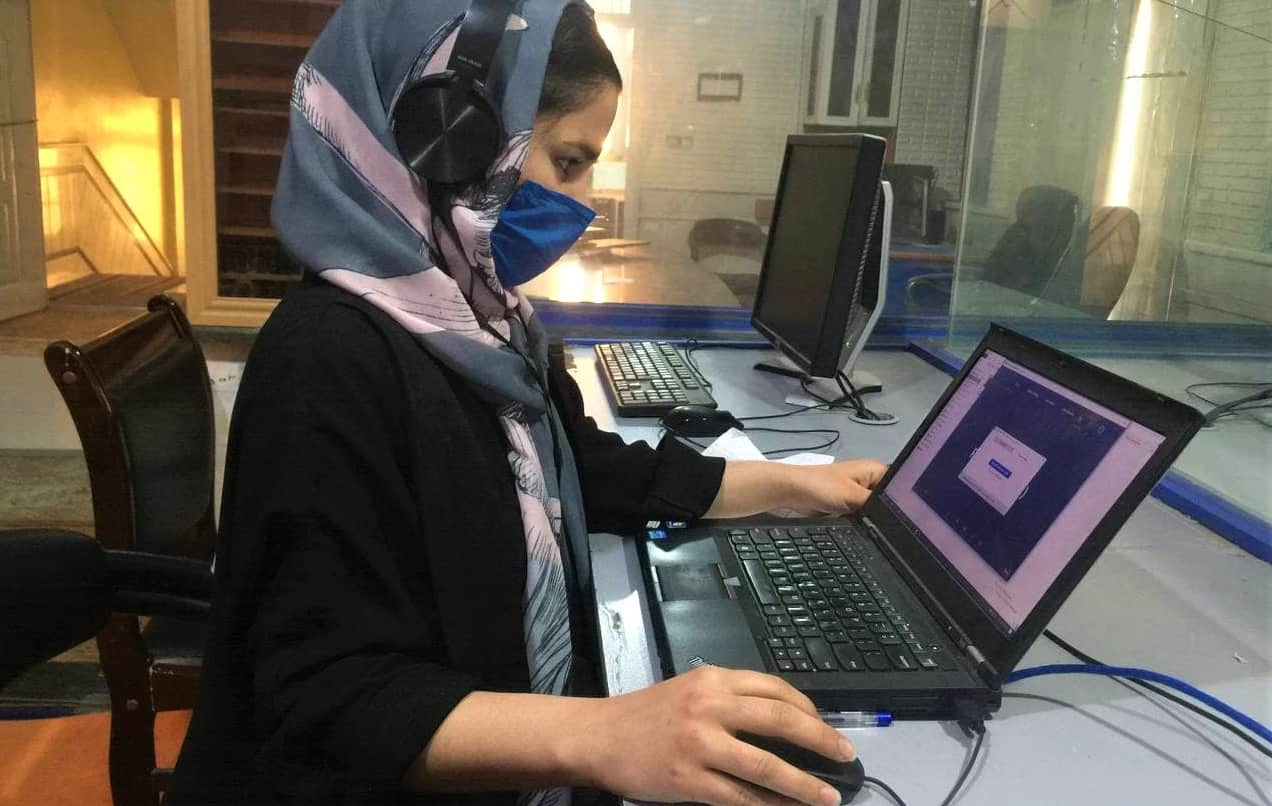 A woman wearing a face mask and a head scarf works on a laptop computer