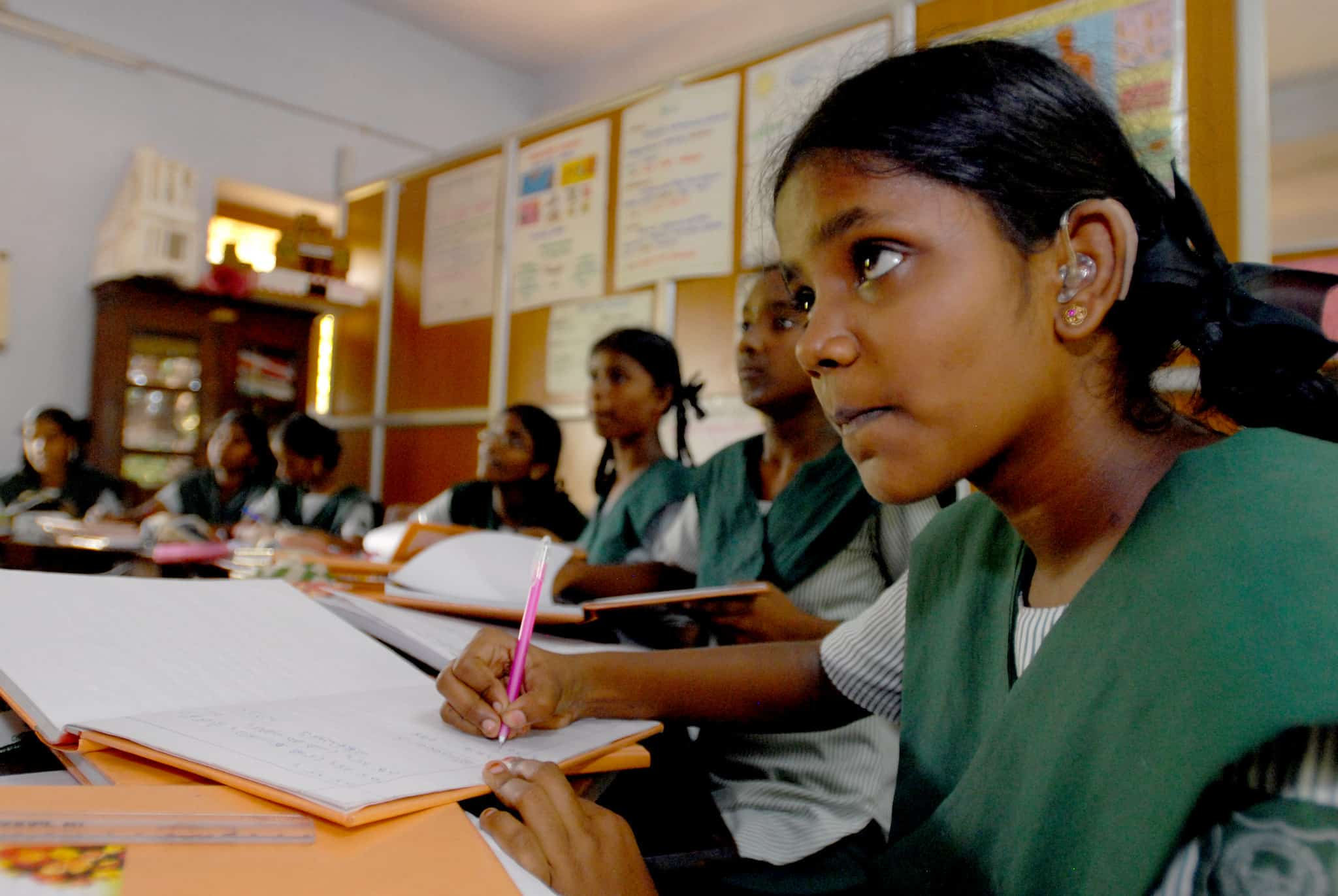 Girls sit at desks in a classroom