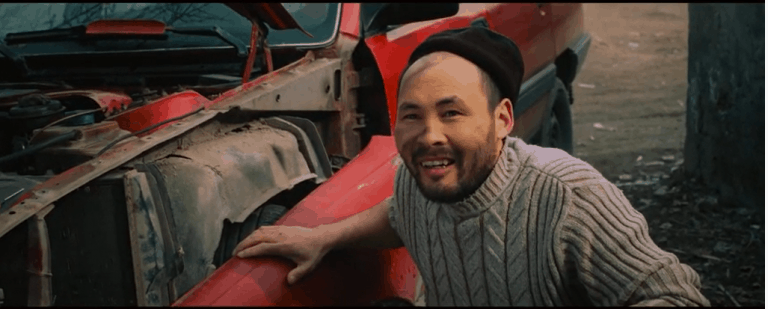 A bearded man wearing a hat puts his hand on the side of a red truck