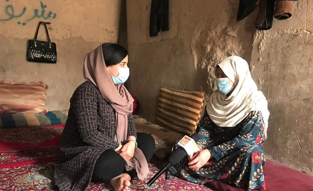 Two women sit inside on a rug talking; both are wearing face masks.