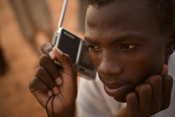 A man holds a portable radio up to his ear