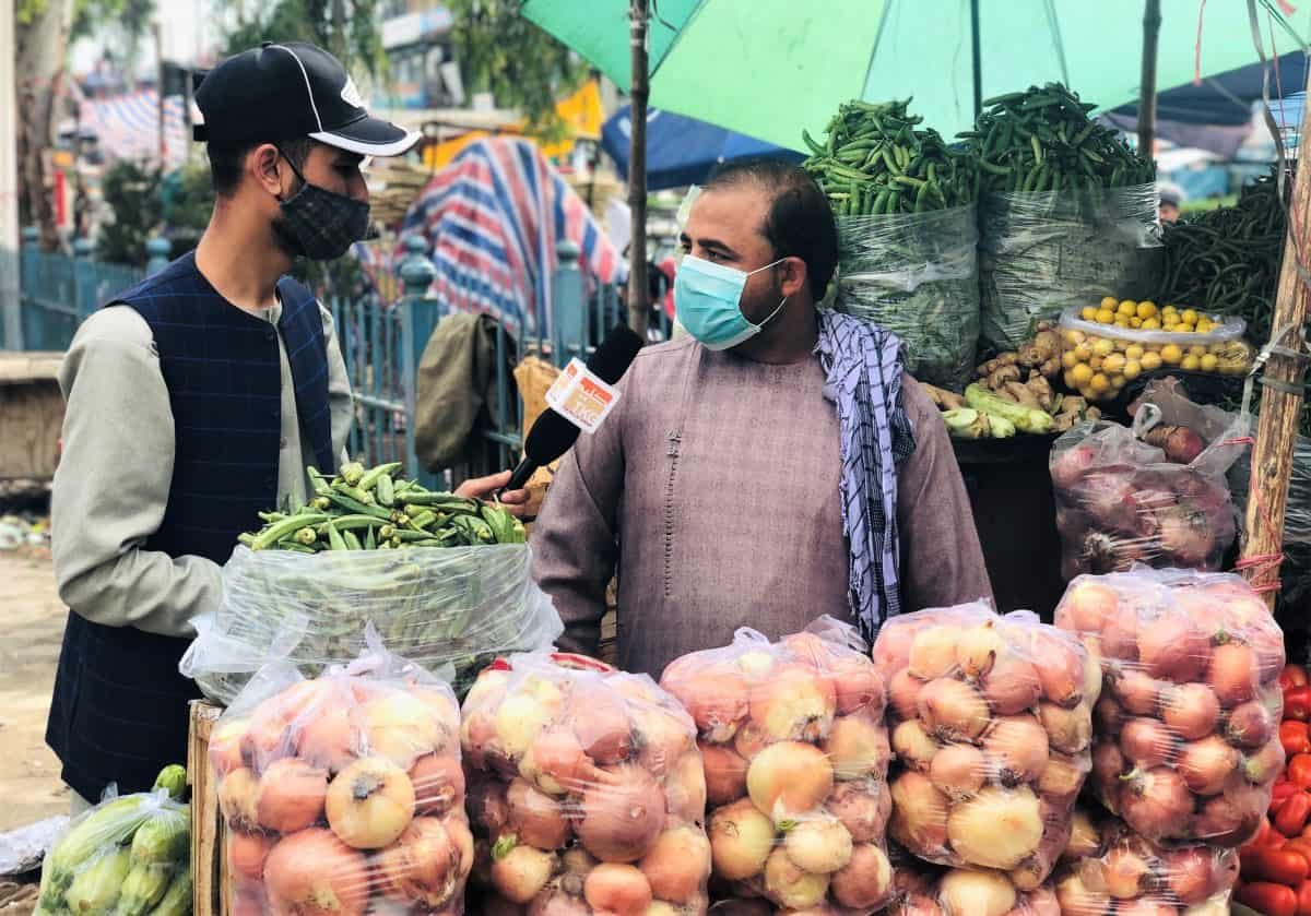 Two men stand by bags of onions in an outdoor market. Both are wearing face masks.