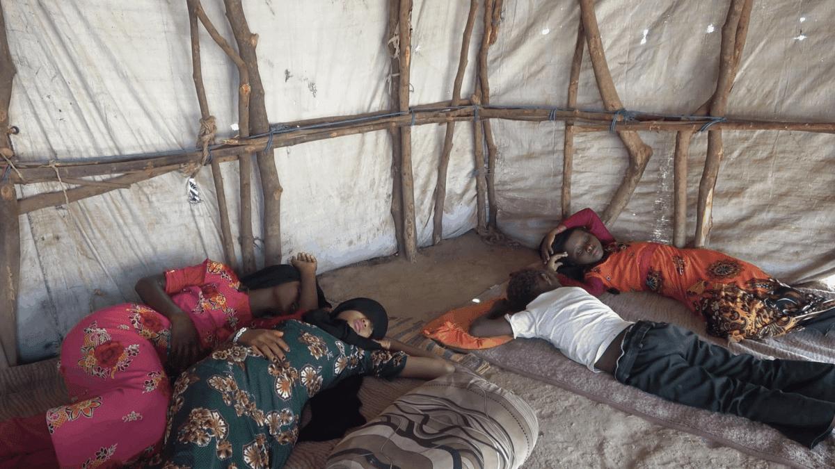 Children lie on mats on the floor of a tent