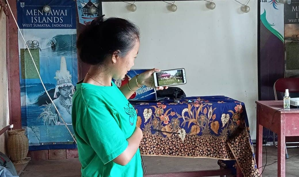 A young woman holds up a smart phone camera to show a video.