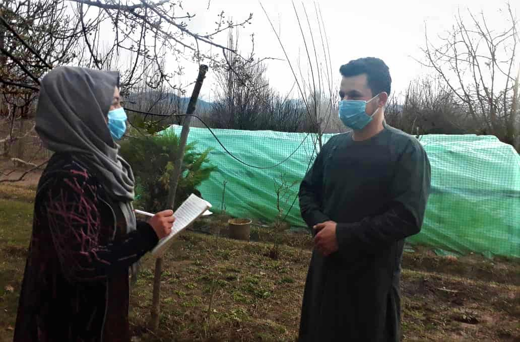 A woman holding a pen and a pad of paper talks to a man; both are wearing face masks.