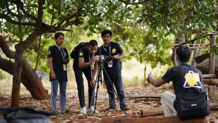 A group of young men use a video camera; they are outside under some trees