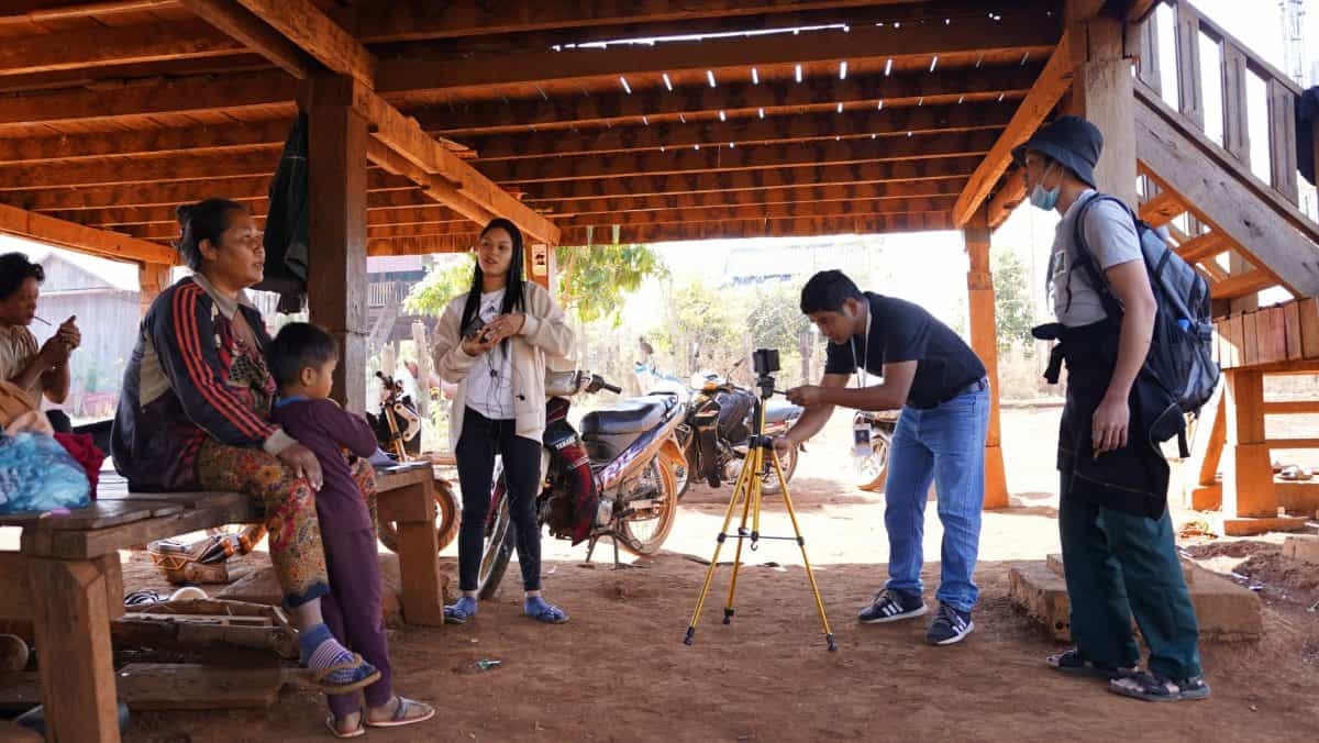 Some young people film a woman and a child under a deck
