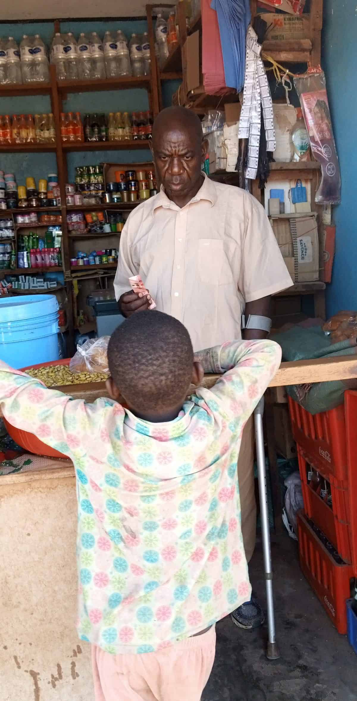 A man stands behind a counter in a store; a young boy looks over the counter on the other side.