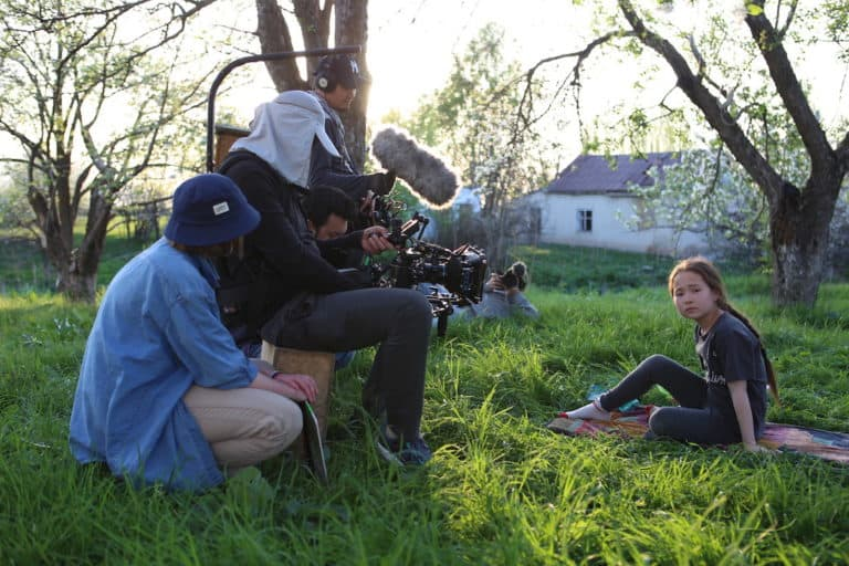 A man films a girl sitting on the grass under a tree
