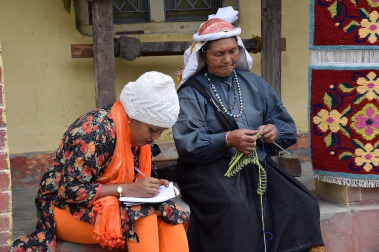 Two women sit together; one is knitting; the other is writing on a notepad.