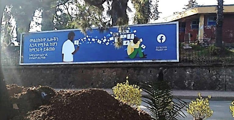 A billboard with Amharic script and a Facebook logo along side of a road.