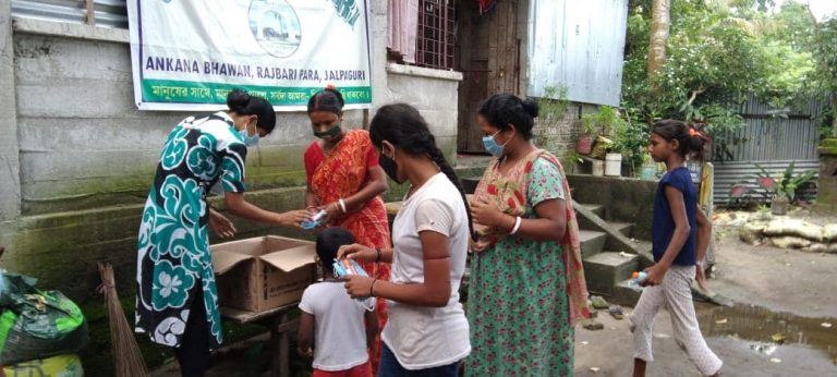 A group of women distribute supplies outside of a house
