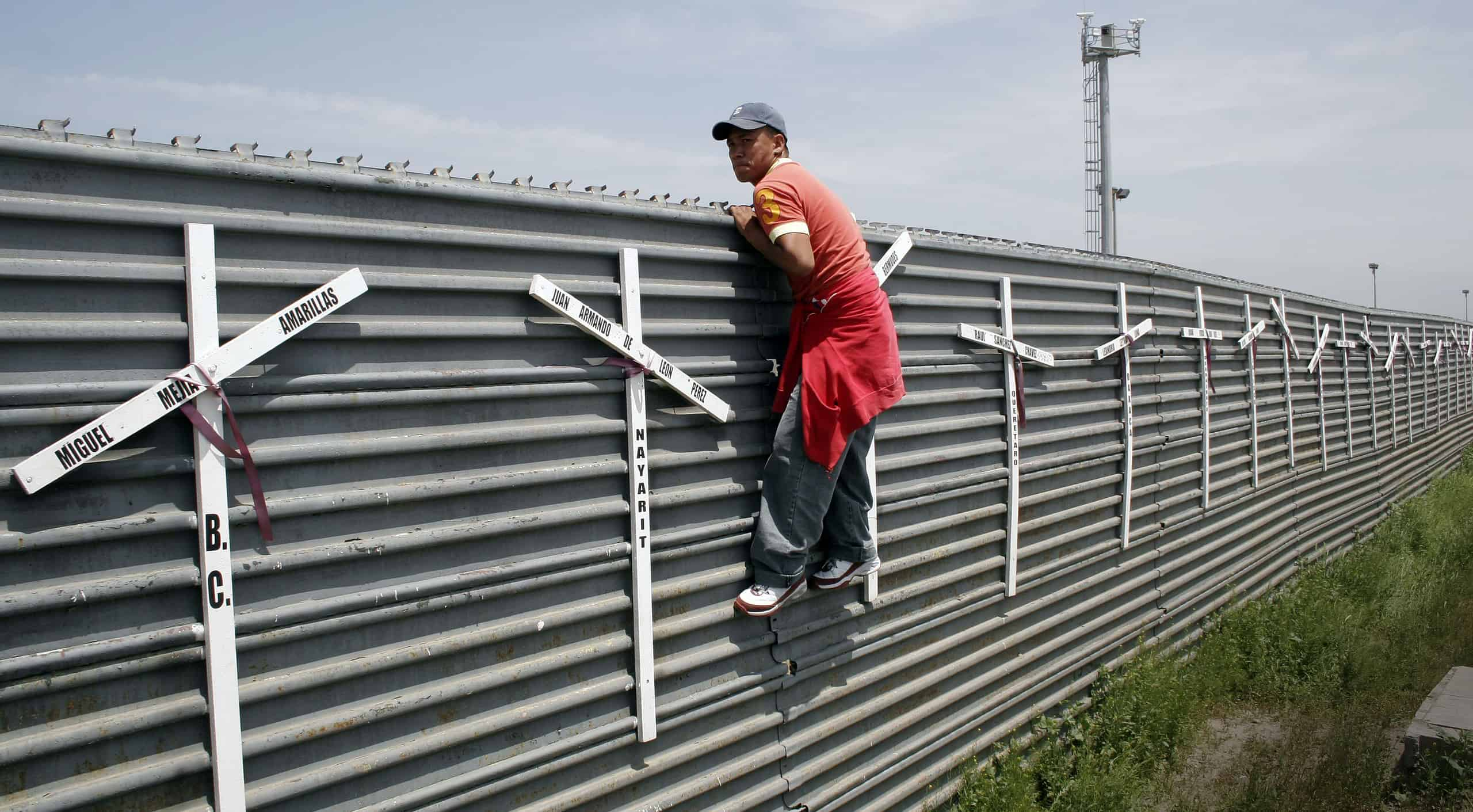 A man holds on to the side of a tall fence. White crosses are attached to the fence.