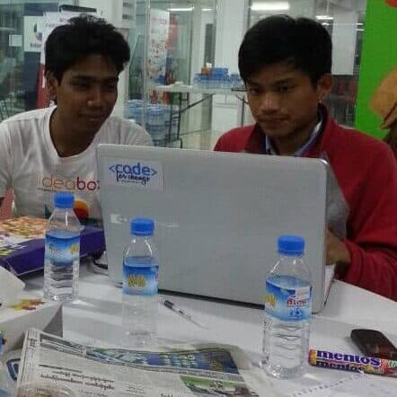 Two young men work together on a computer at a hackathon in Myanmar