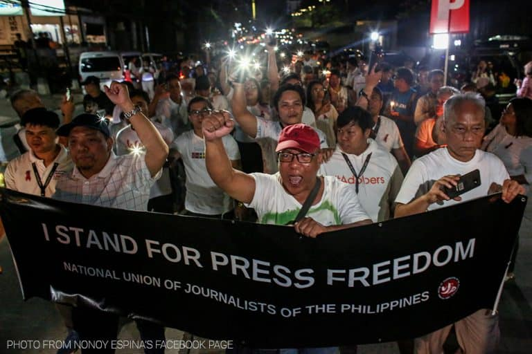 """A protest with a banner reading """"I stand for press freedom."""""""