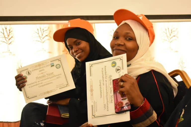 Two women, both wearing orange caps, hold certificates in their hands.