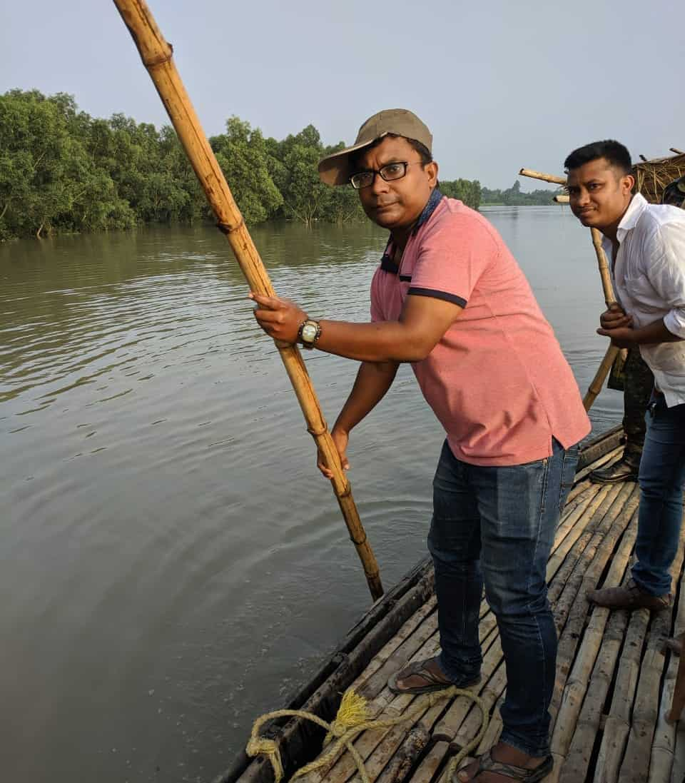 A man holds a long pole while he stands on a barge in a river.