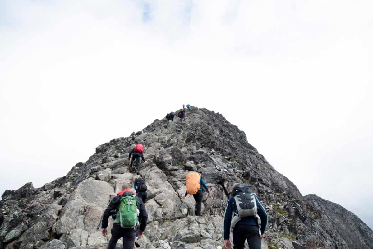 several people wearing backpacks hike up a mountain. at the top of the mountain, other hikers are visible who have reached the summit.