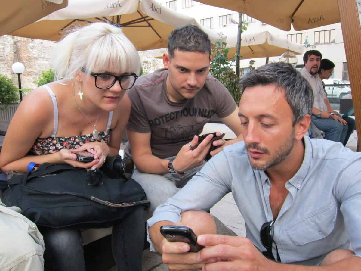 Two men and a woman wearing glasses sit together with their cell phones. The woman and young man look on as the other man shows something on his phone.