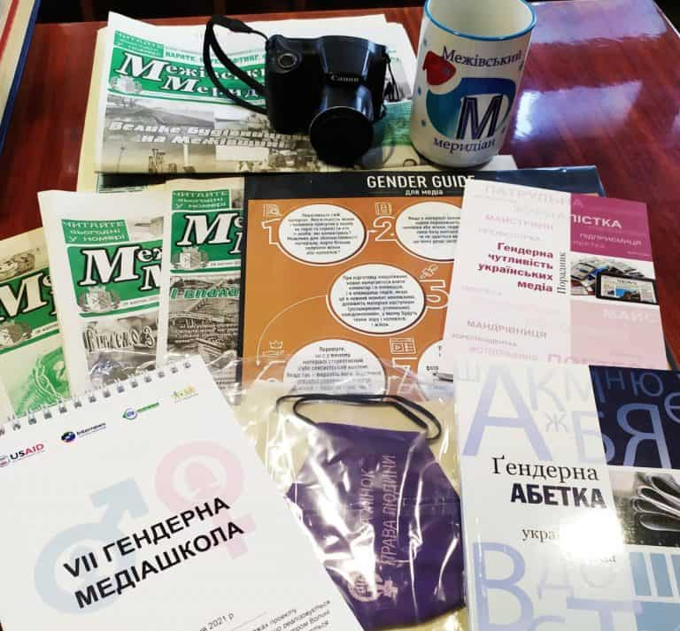 A camera and a mug sit on some newsletters and pamphlets