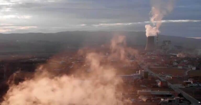 Smoke over a city - a factory in the background emits smoke.