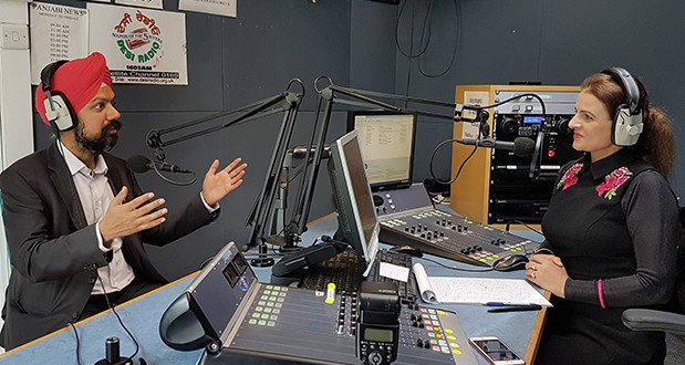 In a radio studio, a man and a woman sit across from each other talking.