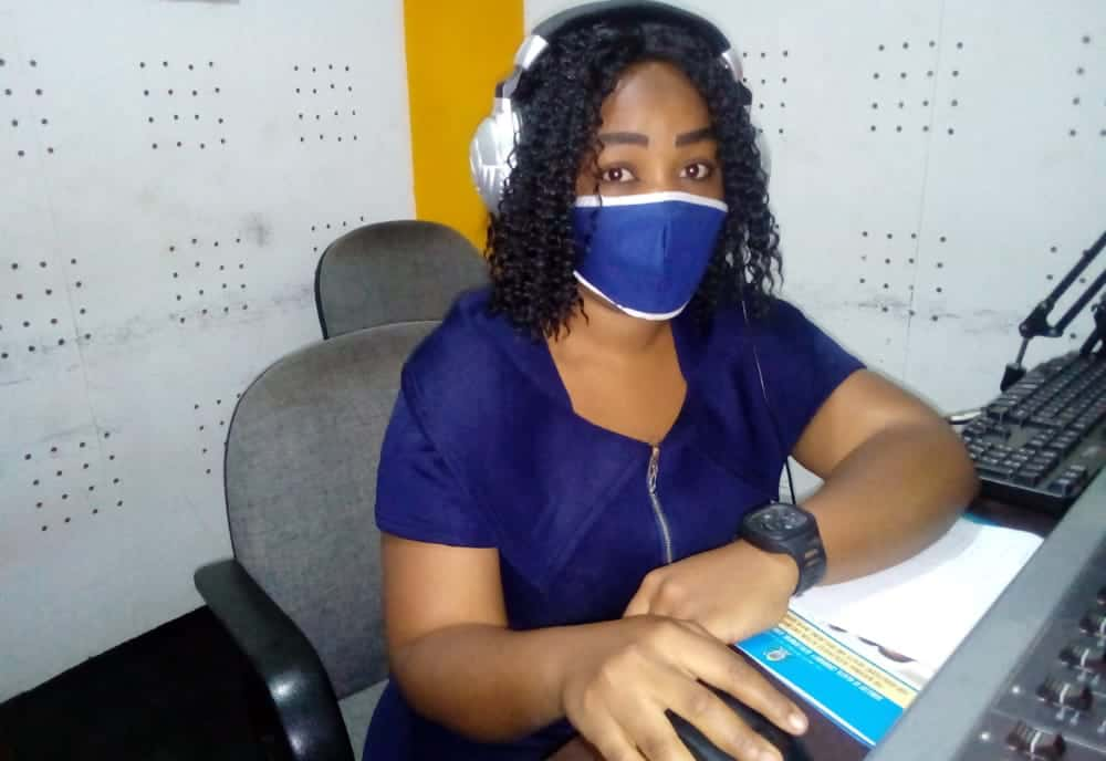 A woman wearing a face mask works on a laptop computer.