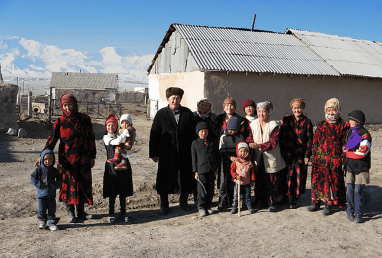 A group of people stands outside a small house.