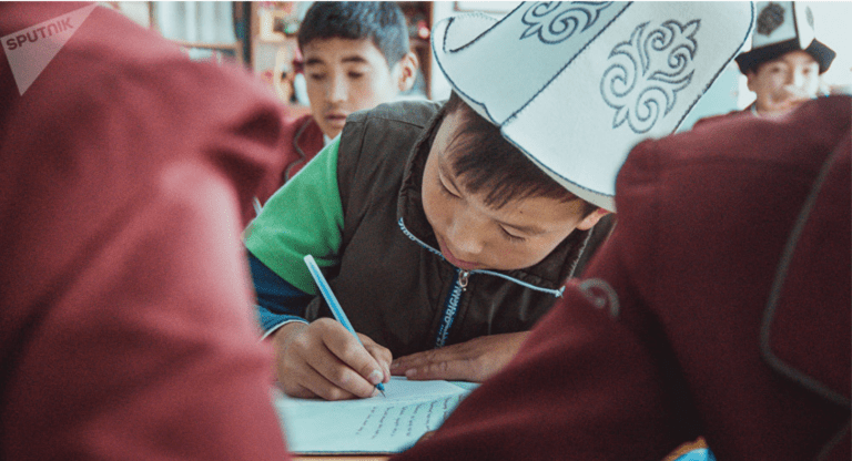 A young boy writes on a paper on his desk in a crowded classroom.