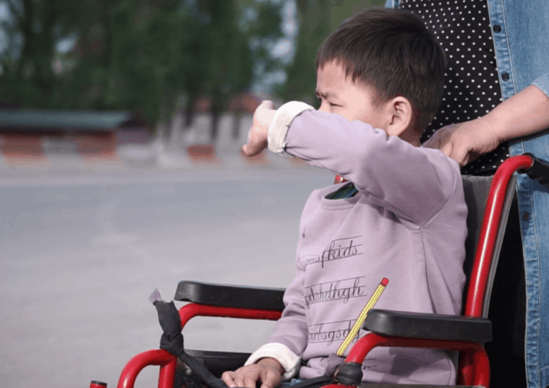 A boy sits in a wheelchair with someone standing behind him.
