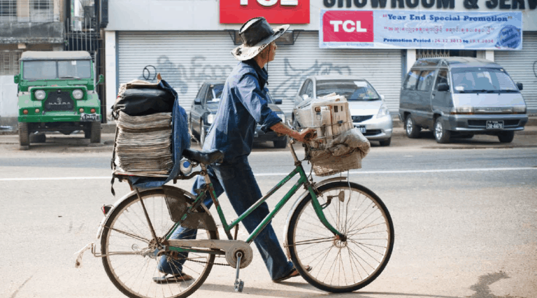 A man walks his bicycle, piled with newspapers, down a city street.