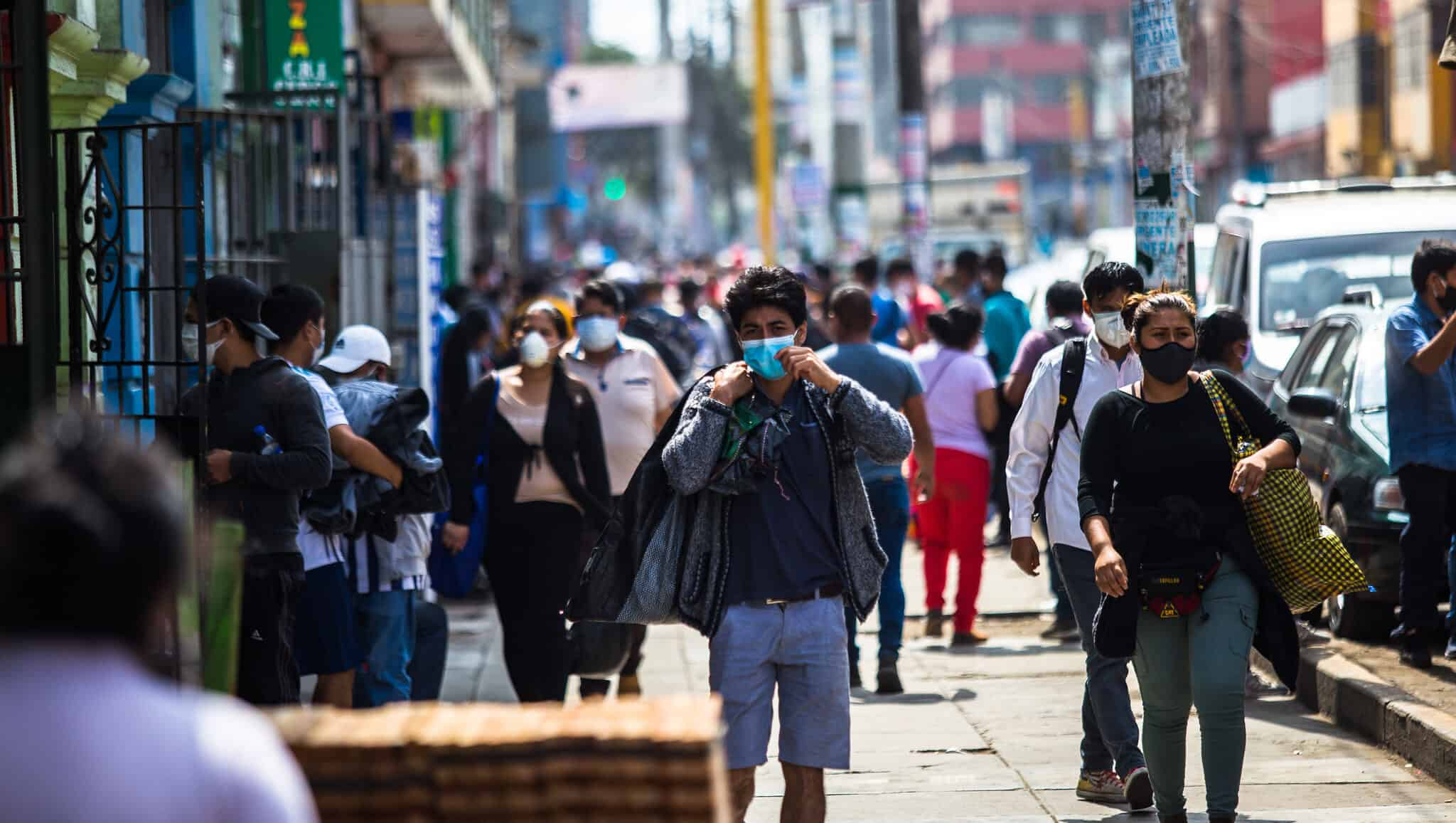 People walk down the sidewalk in a city - most are wearing face masks.