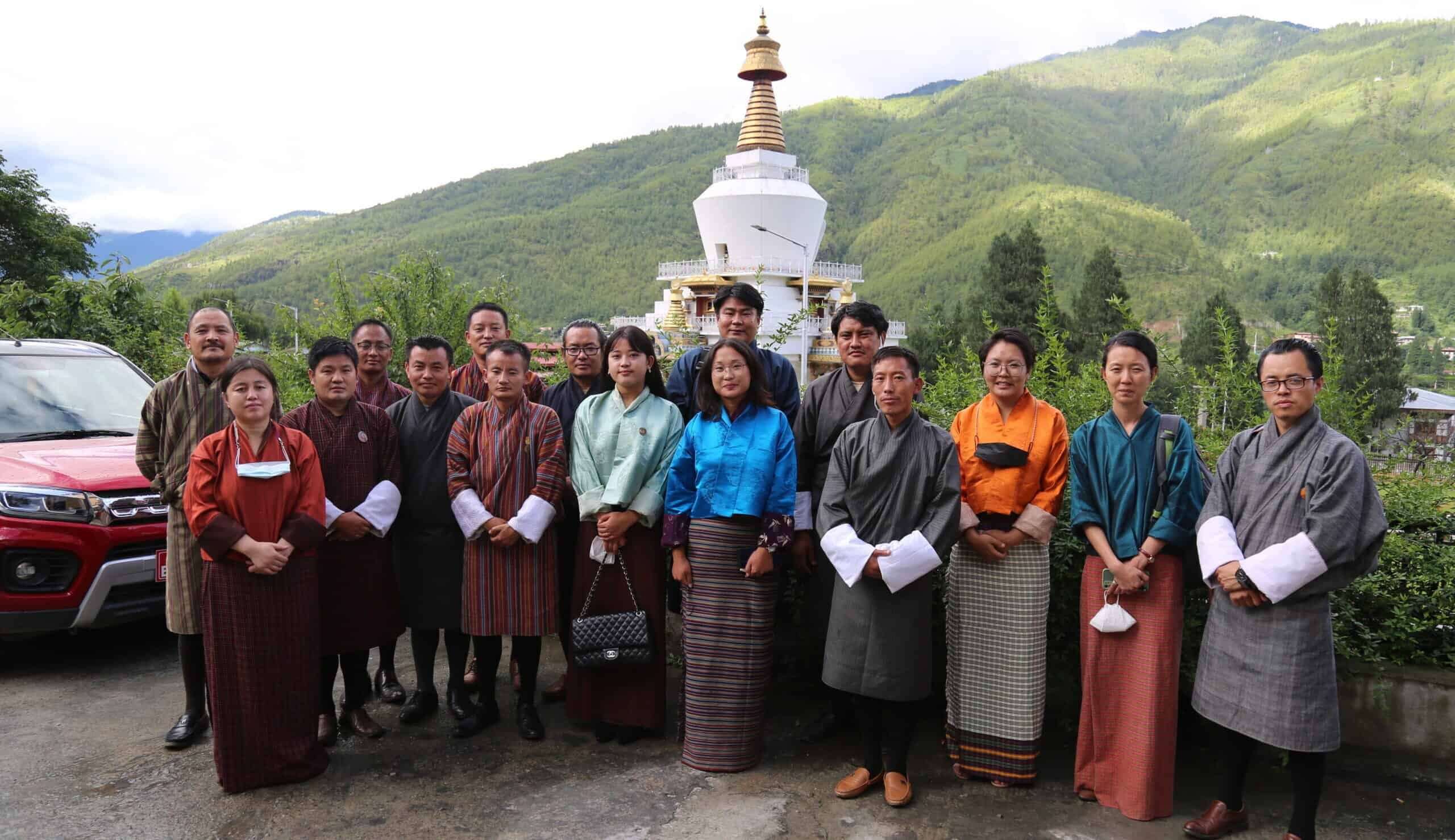 A group of people stand together posing with a temple and green hills behind them.