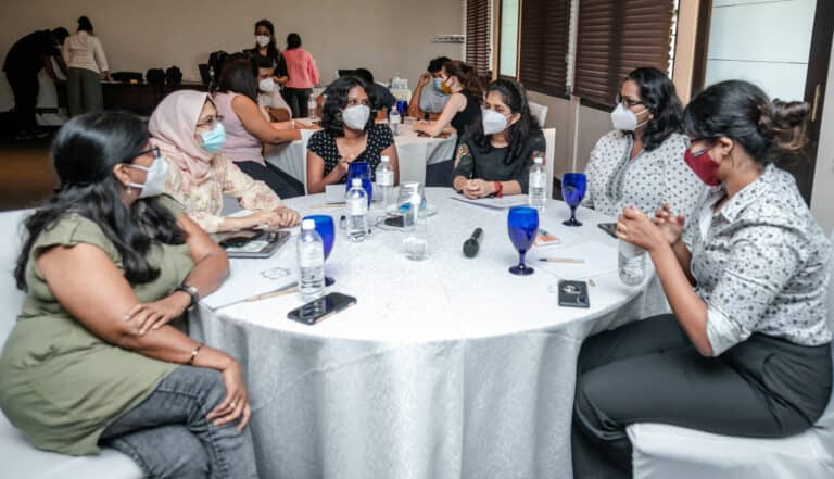 A group of women wearing face masks sit around a table talking.