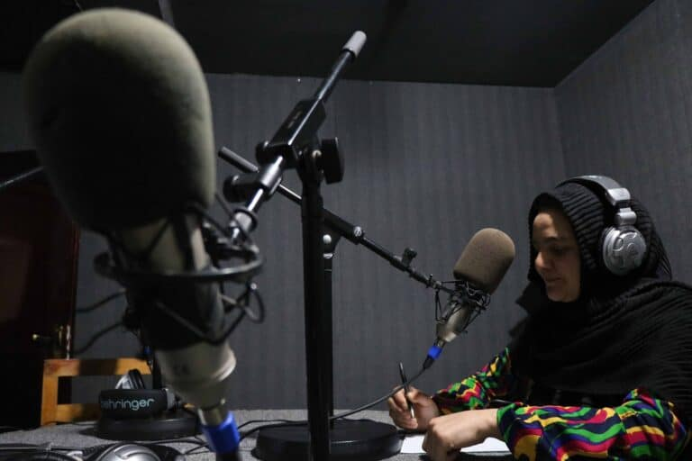A woman sits at a microphone in a radio studio.
