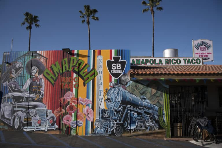 A mural is painted on a wall next to a restaurant called Amapola Rico Taco. The mural includes an old style car with two skeletons standing next to it and a steam engine train.