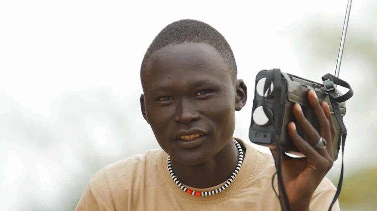 a man listens to a portable radio.