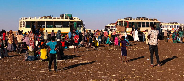 Refugees gather around buses.