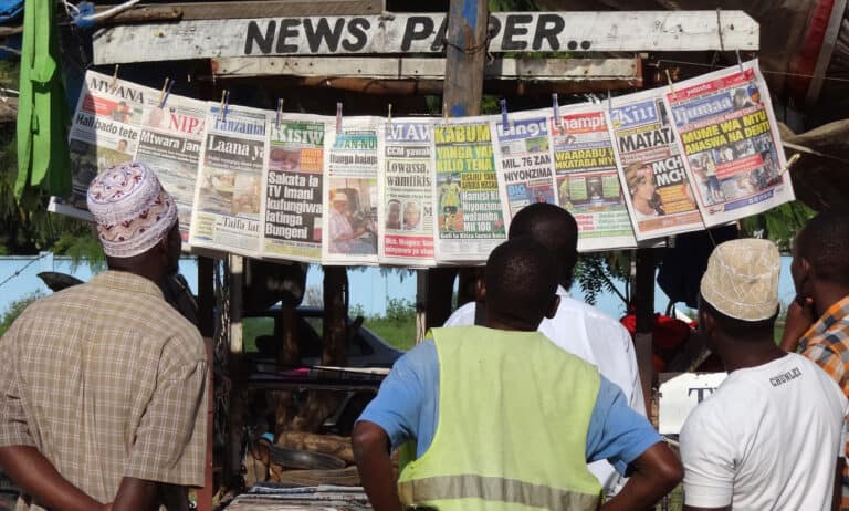 Three men read newspapers at a newstand.
