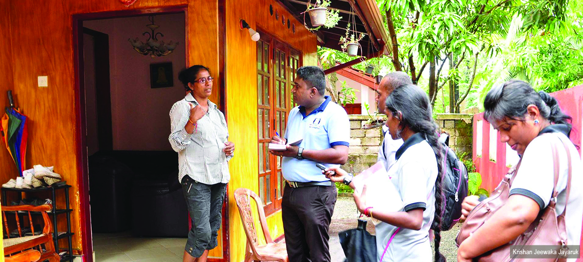 Four journalists stand outside a house interviewing a woman who is standing in the doorway.