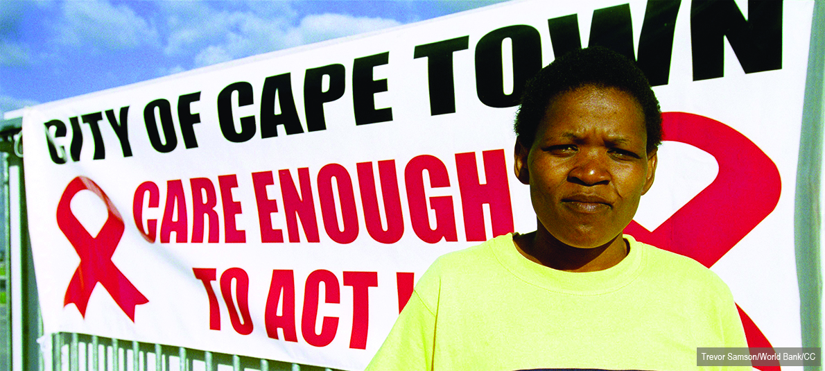 """A woman stands in front of a banner that says """"City of Cape Town – Care Enough to Act."""""""