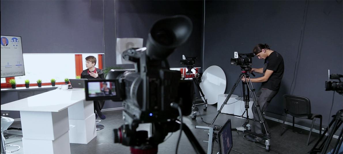 A videographer films a newscaster in a Ukrainian news studio